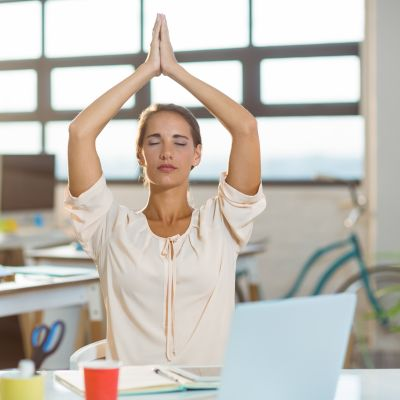 Female business executive performing yoga in office